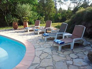 Terrasse ved poolen med liggestole